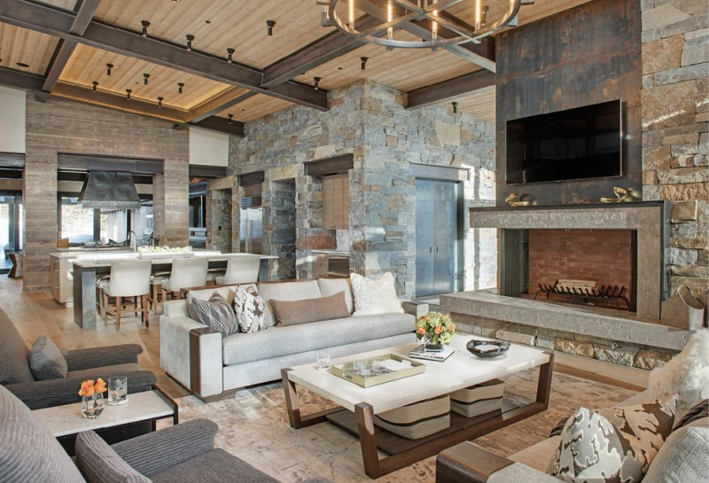 rustic living room with wooden floor, white top square coffee table, grey sofa, stone and wooden textured wall, fireplace