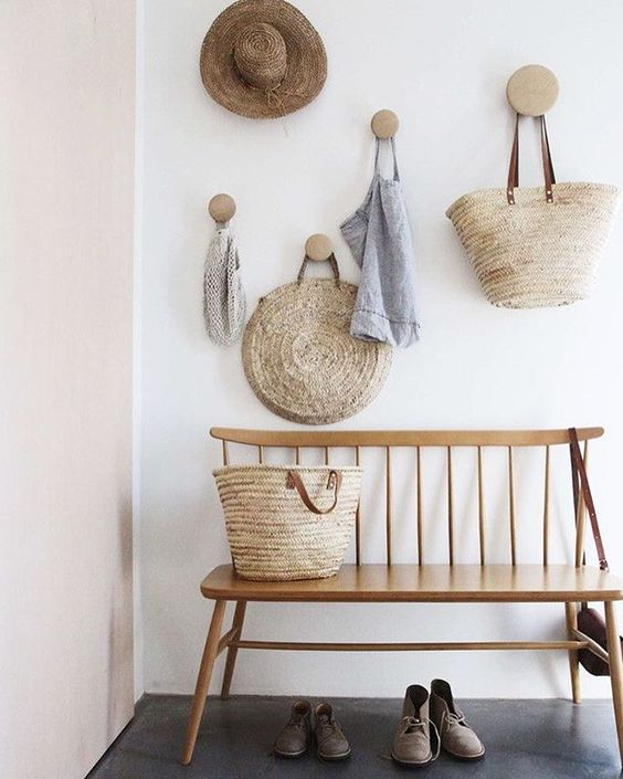simple bench with back on entryways with round wooden hooks on the wall