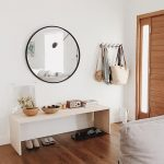 Simple Wooden Bench In Entry Hall With Round Large Mirror, Coat Racks, Pot, Basket, Storage