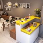 Small Kitchen With Grey Wall, Grey Refreigerator, Grey Floor, Yellow Kitchen Top, Brown Wooden Bench, White Dinner Table, White Midcentury Chairs