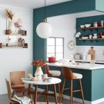 Small Kitchen With Turquiose Wall Surrounded The Kichen, White Wall Inside And Out, White Kitchen Top With Wooden Bar Stool, Wooden Dinner Set With White Top, Shelves