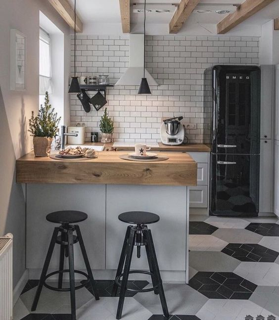 small kitchen with white backsplash, white and black hexagonal tiles floor, white cabinet with brown wooden kitchen top, black stool