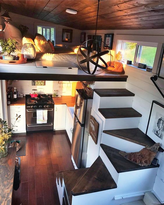 small loft, dark wooden floor, dark wooden stairs, low ceiling bedroom on top, kitchen under with long table