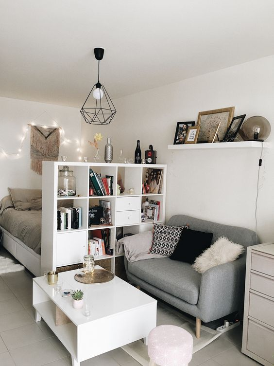 studio apartment room with bedding sith storage, white book shelves, grey sofa, grey flooring, white cabinet, white coffee table, white floating shelf, geometrical wired lamp