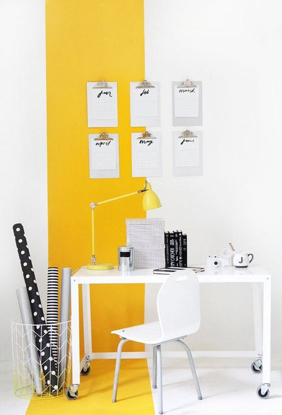 study area, white floor, white wall, yellow accent on wall and floor, white table on wheels, white chair, yellow table lamp