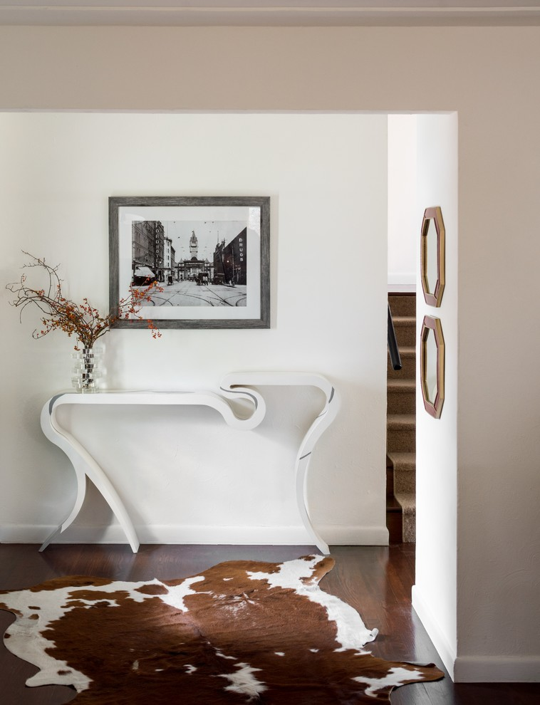 table for entry way cowhide rug wooden floor white walls white table glass flower vase black and white artwork hexagonal wall mirrors stairs