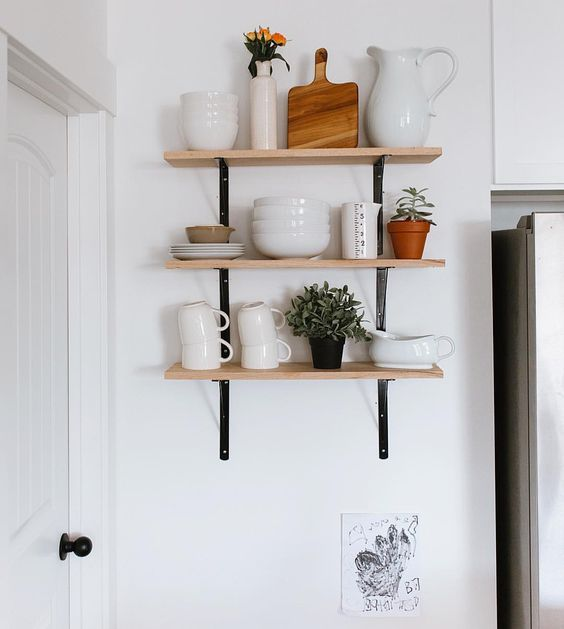 three small high wooden open shelving with black metal support on white wall