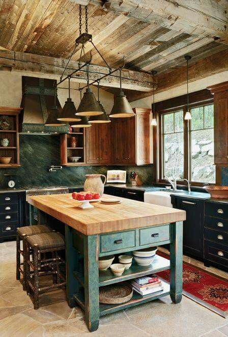 traditional kitchen with dark green cabinet, dark green wall, brown wooden cabinet on top, green island with brown wooden top, industrial chandelier