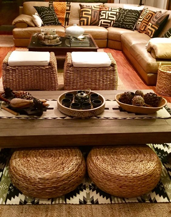 tribal pattern on pillows, brown leather sofa, rattan ottoman, rattan square stools with white cushion, square coffee table glass top, rug