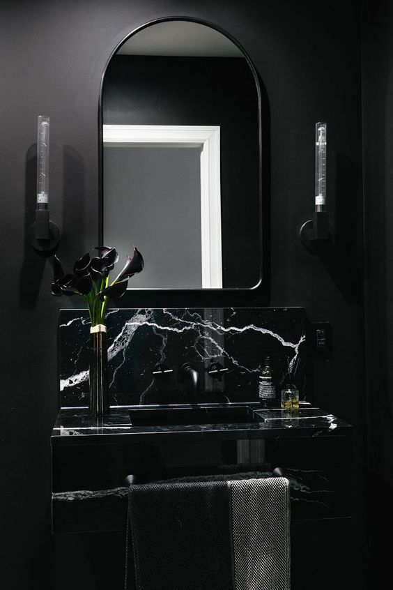 vanity with black marble, black faucet, black framed mirror, black painted wall