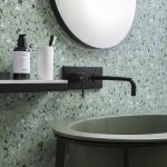 Vanity With Muted Green Basin, Black Floating Shelves, Black Faucet, Round Mirror, Green Terrazzo Wall