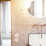 Vanity With Warm Orange Terrazzo Wall, White Sink, Round Mirror, Pendant