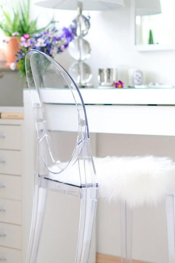 vanity with white table, white lamp, mirror, white cabinet, acrylic chair with white fur