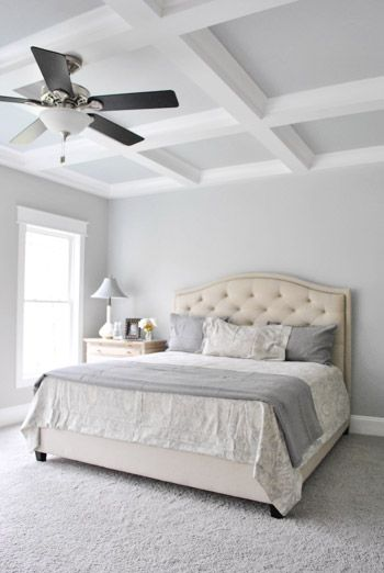white bedroom, rug, bed, platform, white wall, white coferred ceiling, lamp fan ceiling