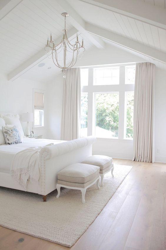 white bedroom, wooden floor, white bedding, white platform bed, white stools, white wooden arch ceiling, white curtain, white rug, chandelier