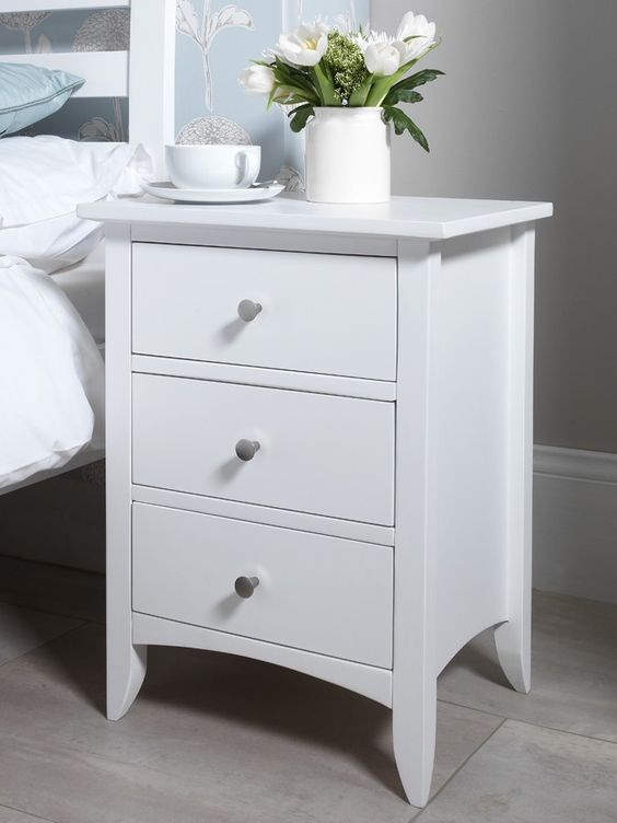 white bedside cabinet with three drawers, vase on top