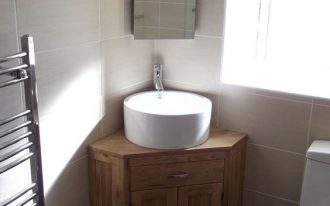white sink on top of brown wooden cabinet with a square mirror placed on the corner