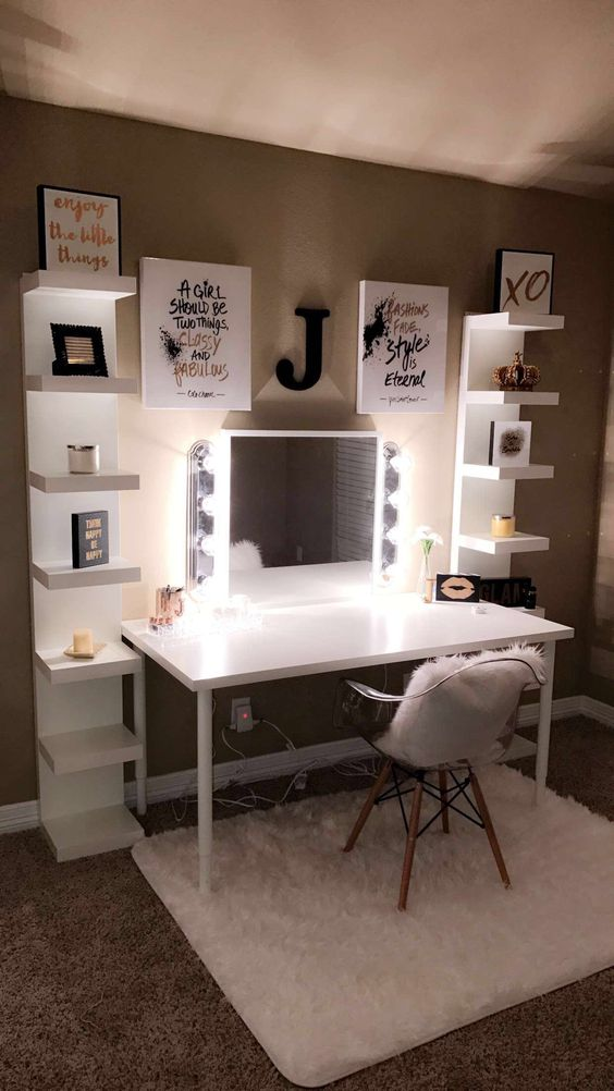 white table, white shelves on right and left, mirror with lamp, pictures, clear midcentury chair with white faux fur