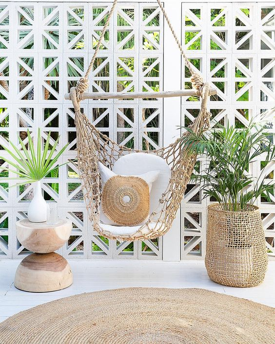 white wooden floor, rattan rug, wooden side table, basket, rattan swing chair