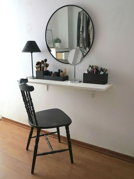 white wooden shelves for vanity, black boxes for cosmetics, black framed mirror, lamp, black chair