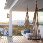 Wooden Bench Swing On The Balcony With Wooden Floor, White Wall, White Chair