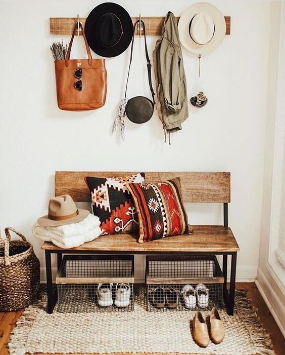 wooden bench with back, metal support in an entryways with wooden floor, white wall, rug, rattan basket, metal basket for shoes, coat racks