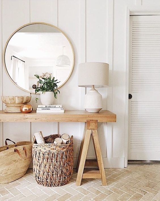 wooden simple bench table with white lamp, rattan basket, bag, round wall mirror