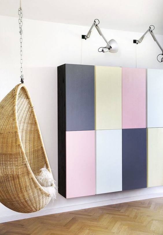 8 colorful floating ivar cabinet on white wall, wooden floor, rattan hanging chair