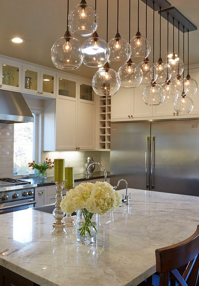 a line of glass bulb pendants above white marble kitchen island's counter top, aluminum fridge, white cabinet, wooden chairs