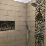 A Line Of Pebbles On The Shower Wall And Shampoo Niche, Glossy Wall Tiles, Silver Faucet