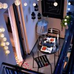 Balcony, Grey Floor, Black Fence, White Wall, Wall Decoration, Black Fake Pendants, Fairy Light, Round Black Metal Dining Set