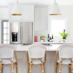 Bar Stools With White Seating On Rattan Legs, White Island, White Cover Pendants, White Cabinet, White Kitchen Top