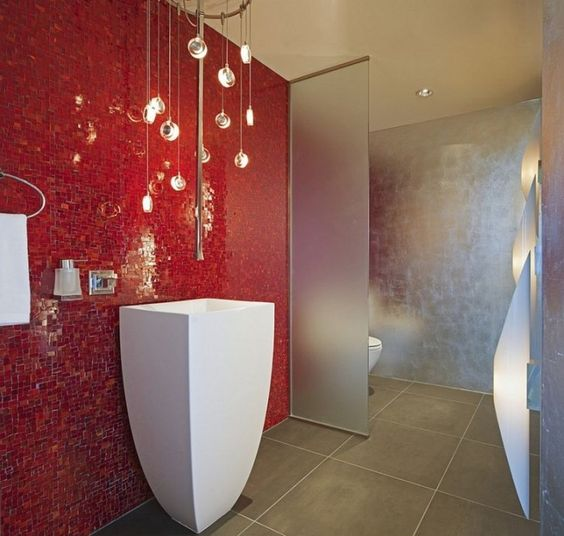 bathroom, grey floor tiles, red mosaic wall tiles, acrylic partition, white toilet, white sink, chandelier
