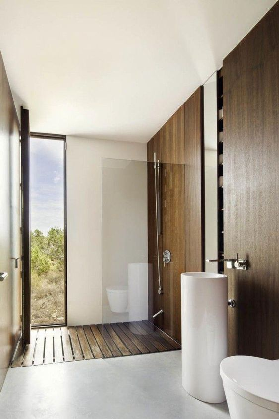 bathroom, grey floor, white tall sink, white toilet, wooden floor, wooden wall, shower area, door to outside