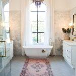 Bathroom, Grey Herringbone Floor Tiles, Warm Marble Wall, Tall Window With Curtain, White Cabinet, Mirror, Moroccan Rug, Shower Area