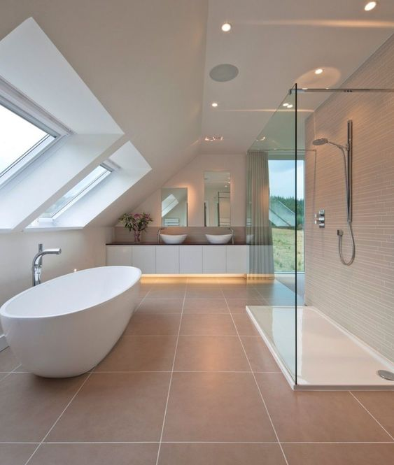 bathroom, large beige floor tiles, white wall, white sloping ceiling, glass windows on sloping ceiling, white tub, shower area, white cabinet with led, white sinks
