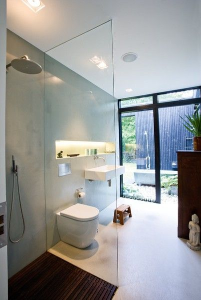 bathroom, white floor, grey wall, wooden floor in shower area, white toilet, white floating sink, built in shelves, tub and shower outside