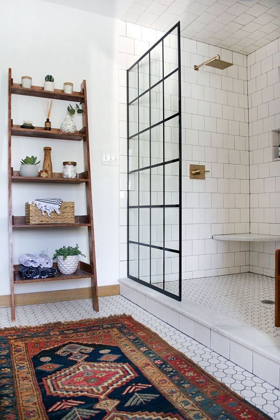bathroom, white geometric floor tiles, rug, wooden rag, glass divider, white square wall tiles