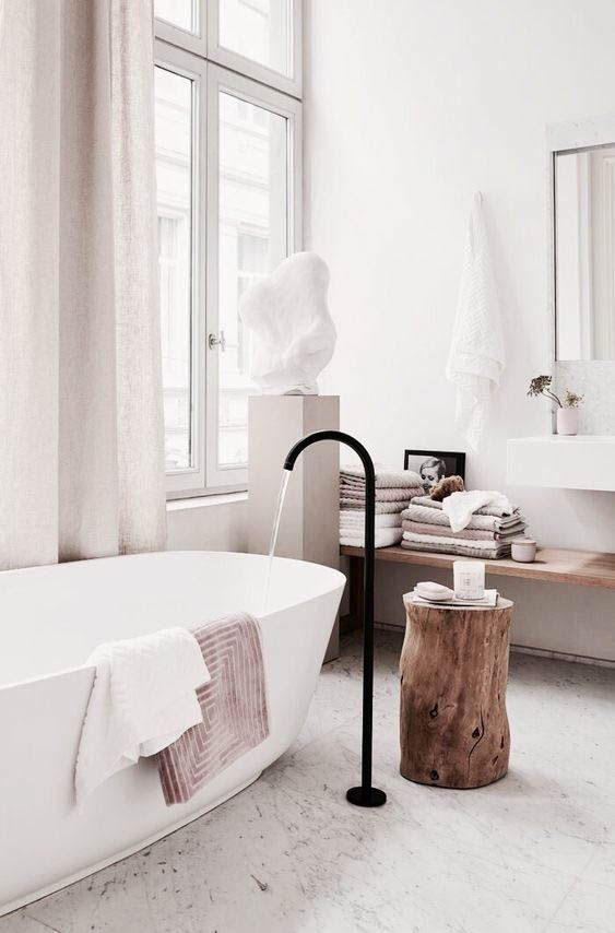 bathroom, white marble floor, white wall, wooden floating shelves, white sink, mirror, white rub, black faucet, windows with curtain