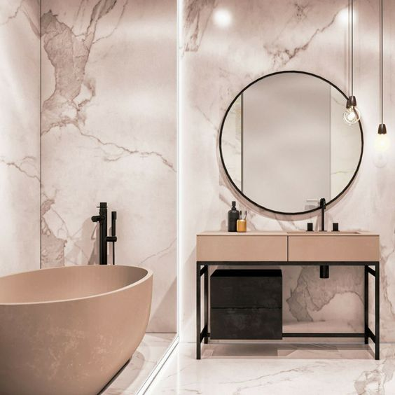 bathroom, white marble with pinkish pattern, beige vanity table with built in sink, black faucet, beige tub with black faucet, round mirror, pendants