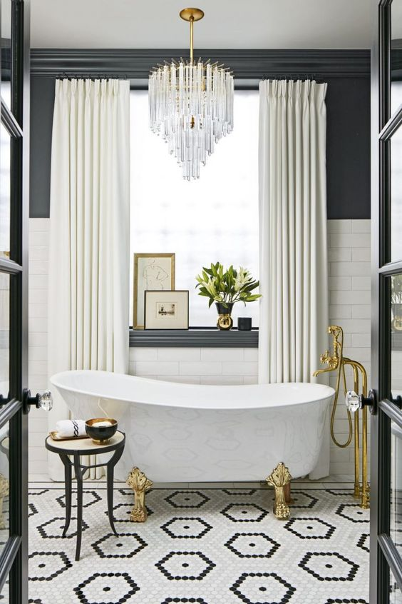 bathroom, white tub with golden legs, golden faucet, tiny hexagon tiles in hexagon pattern, white subway wall tiles, dark grey wall