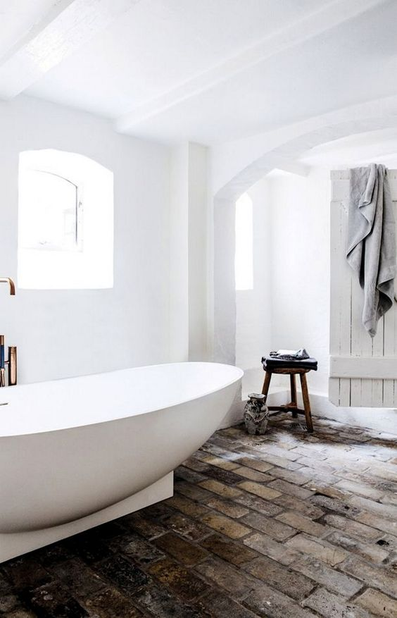 bathroom, white walls, white ceiling, white tub, old rustic subway floor tiles, white wooden door, stool