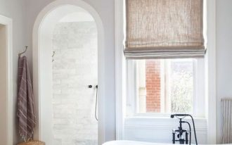 bathroom, wooden floor, white sink, white wall, window with roman shade, slim golden chandelier, rattan basket, rug