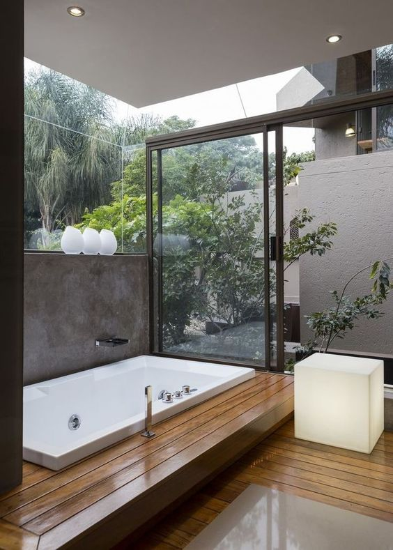 bathroom, wooden planks floor, white tub, glass wall, glass sliding door, white ceiling