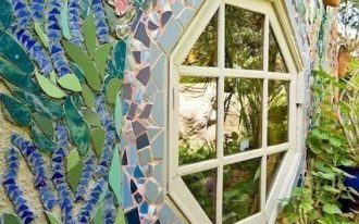beautiful mural on exterior wall around an octagon window