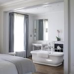 Bedroom And Bathroom In Open Space, White Bed, Wooden Floor, White Tub, White Wall, Grey Curtain, White Sink, Mirror