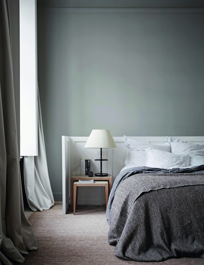 bedroom, beige flooring rug, sage green wall, white wooden wraparound headboard, grey bedding, wooden bedside table, white cover table lamp, grey curtain
