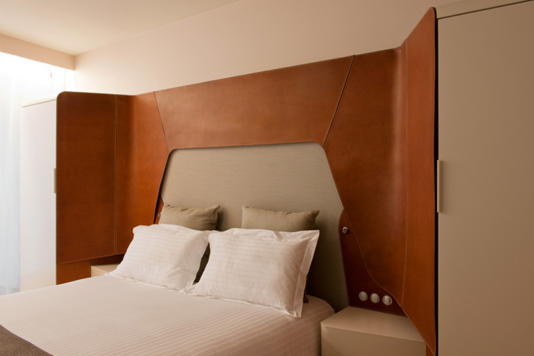 bedroom, beige wall, white bedding, wooden smooth designed wraparound headboar, built in cupboard