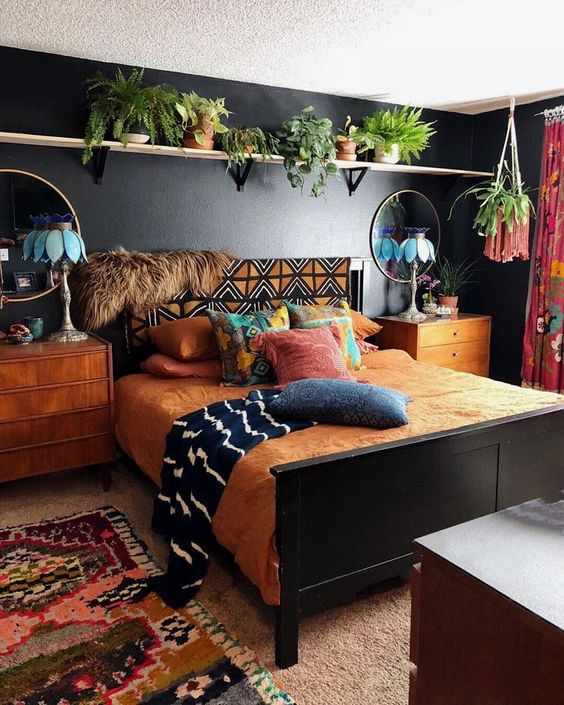 bedroom, beige rug, colorful rug, warm brown bedding, dark grey wall, floating shelves for ponts, wooden cabinet on bedside, round mirrors, blue table lamps