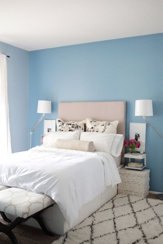 bedroom, blue wall, pink beige headboard, white ebdding, white rug, white bench, white rattan side table, floor lamp